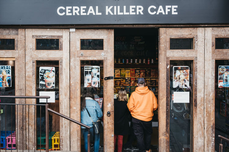 People entering Cereal Killer cafe in Camden, London, the Worlds first International Cereal Cafe. Communication Three Quarter Length City Outdoors Lifestyles Rear View Window Standing Building Exterior Real People Cafe Cereal Killer Tourists People Leisure Activity Travel Destinations Europe England Market Famous Place Weekend Activities Trabel Camden Market, London Camden Town Uk London