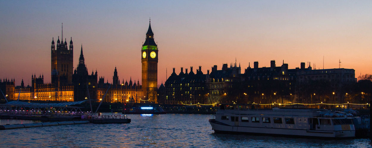 Panoramic view of illuminated big ben by thames river during sunset