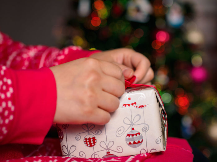 Cropped image of woman unwrapping gift during christmas