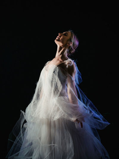 Ballet Dancer Wearing White Dress Dancing Against Black Background