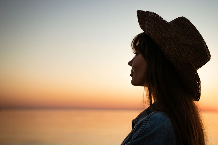 Portrait of a young woman by the sea in a hat at sunset