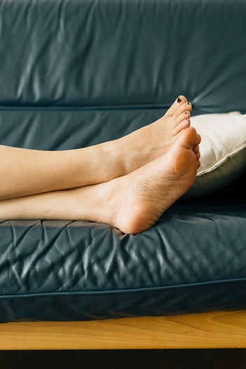 Low section of woman relaxing on sofa