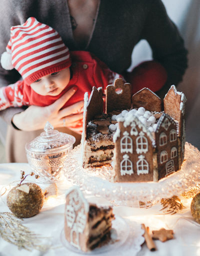 Midsection of mother with baby in front of dessert at table during christmas