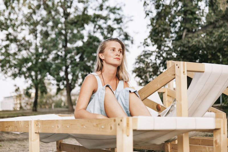 Portrait of woman sitting on table against trees
