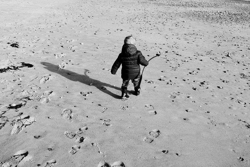 Rear view of kid walking with shadow on wet shore at beach