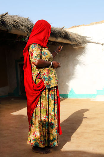 Side view of woman in traditional clothing standing outside house