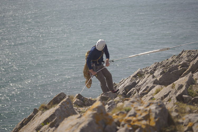 High angle view of man climbing on mountain against sea