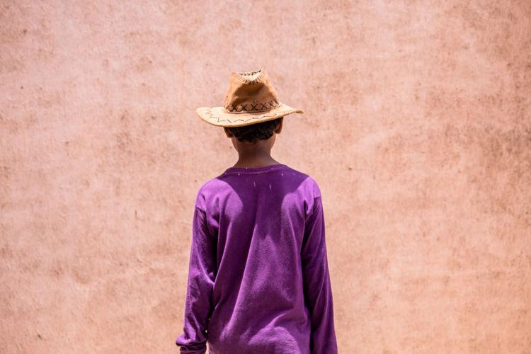 Rear view of teenage boy wearing hat against wall