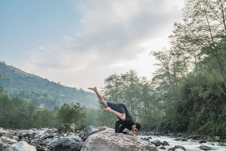 Man doing yoga on rock at riverbank in forest