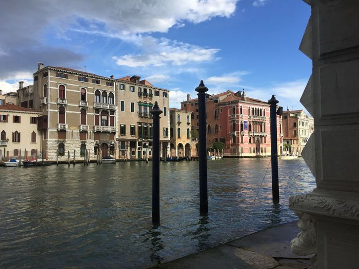 Buildings by grand canal against sky in city