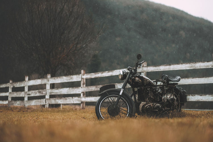 Abandoned motorcycle on field against trees