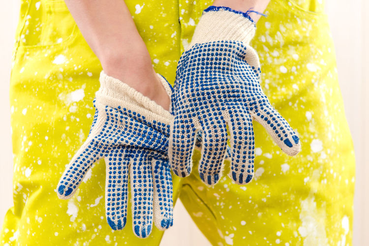 Midsection Of Woman In Dirty Coveralls Wearing Gloves Paintbrush While Standing Against Wall