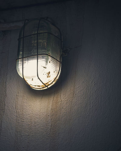 Low angle view of light bulb hanging on wall