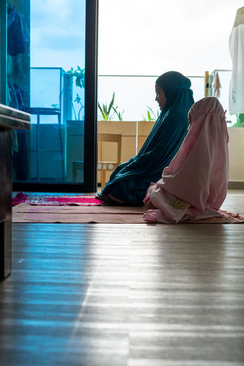 Side view of woman sitting on floor
