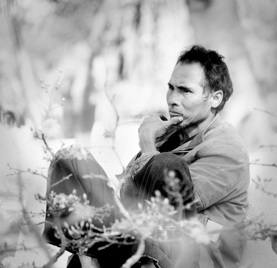 Thoughtful man sitting on plants