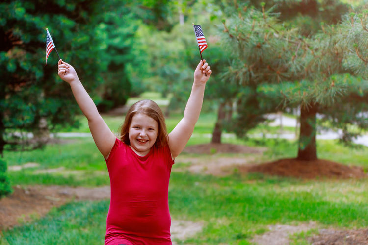 Portrait Of Smiling Girl Holding America Flags While Standing At Park