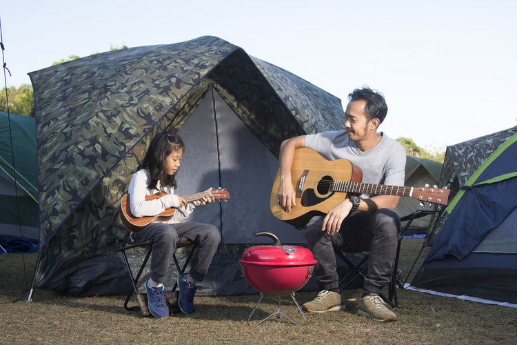 Father and daughter playing guitars against tents