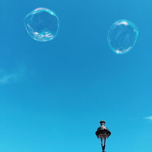 Low Angle View Of Bubbles Against Blue Sky