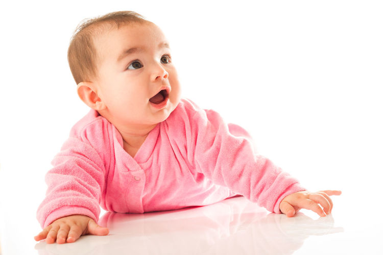 Cute baby girl with pink face against white background