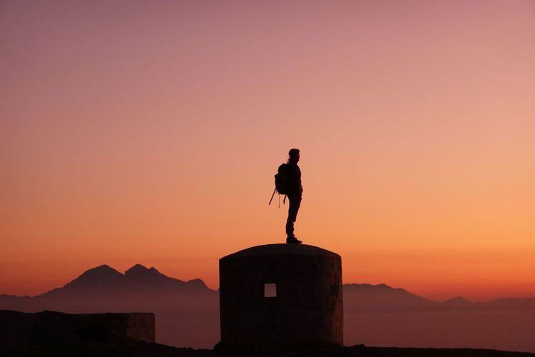 Silhouette man standing on built structure against orange sky