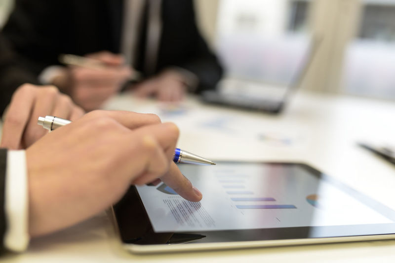 Close-up of a modern business team using tablet computer to work with financial data Graphic Tablet Business Businesspeople Busness Close-up Computer Day Desk Human Hand Indoors  One Person Pen People Real People Selective Focus Tablet Computer Working Writing