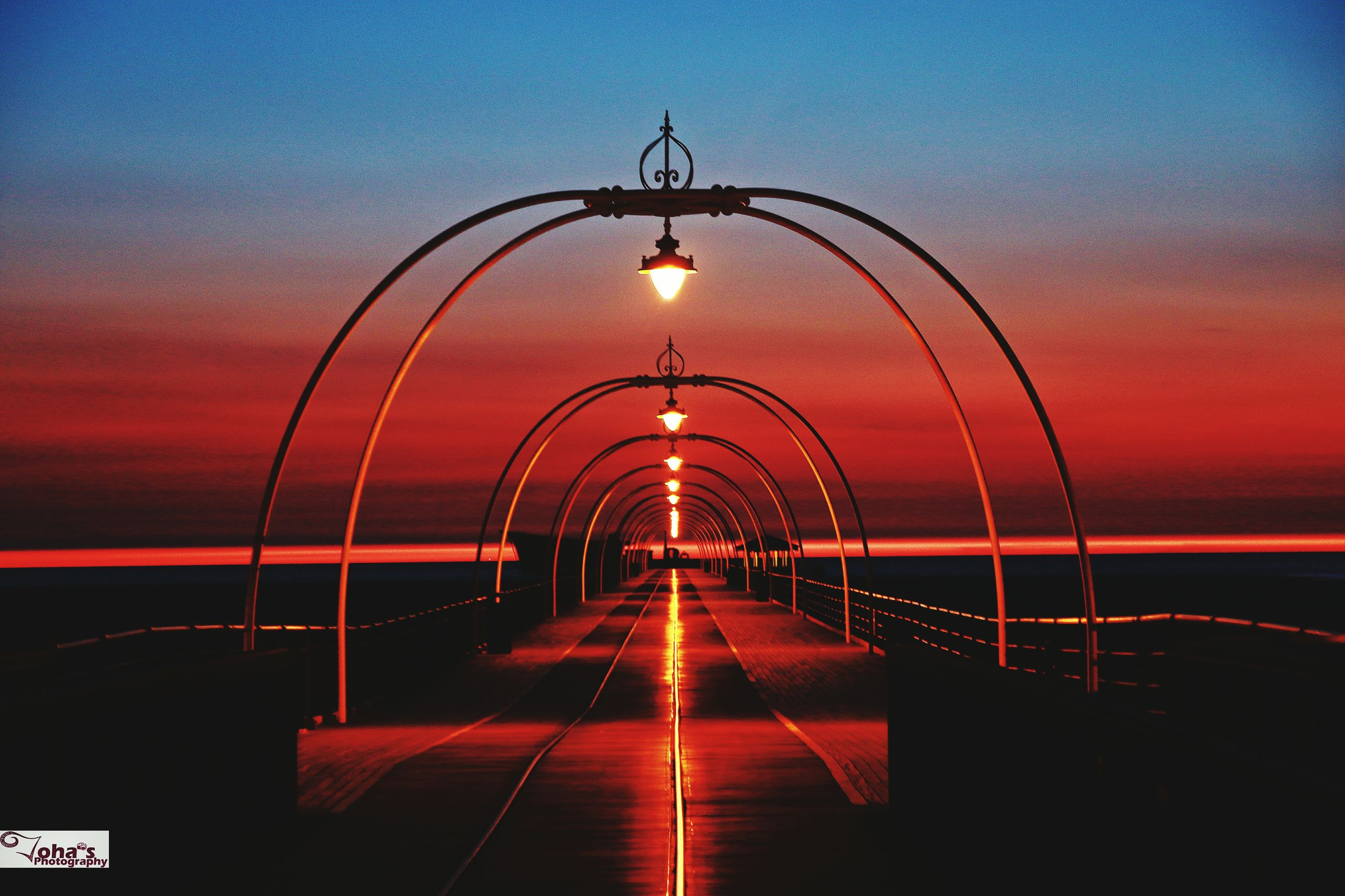 the way forward, illuminated, sunset, lighting equipment, street light, arch, diminishing perspective, in a row, long, bridge, tranquility, electric light, tranquil scene, sky, surface level, sea, vanishing point, arched, scenics