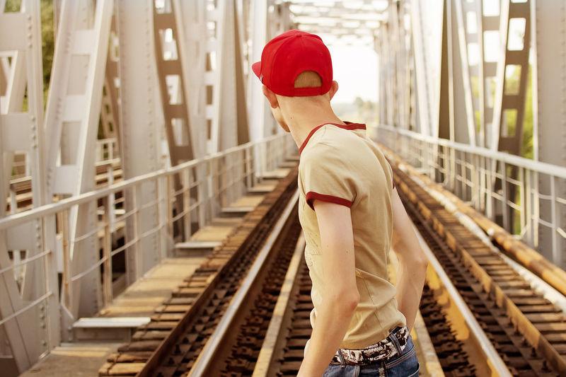 Rear view of teenage boy standing at railway bridge
