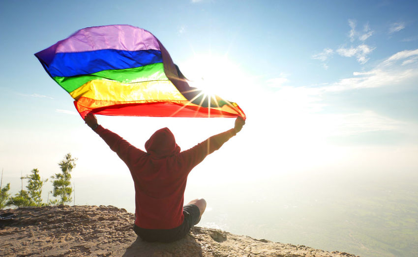 pride! Adult Arms Raised Beauty In Nature Day Environment Human Arm Land Leisure Activity Lgbt Lifestyles Multi Colored Nature One Person Outdoors Pride Rainbow Flag Real People Rear View Sky Sunlight Trip Vacations Water Wind