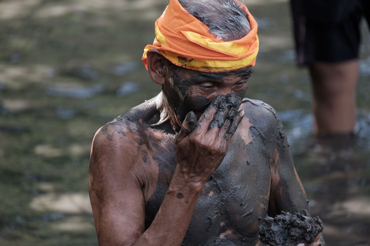 Close-Up Of Shirtless Man Applying Mud On Body