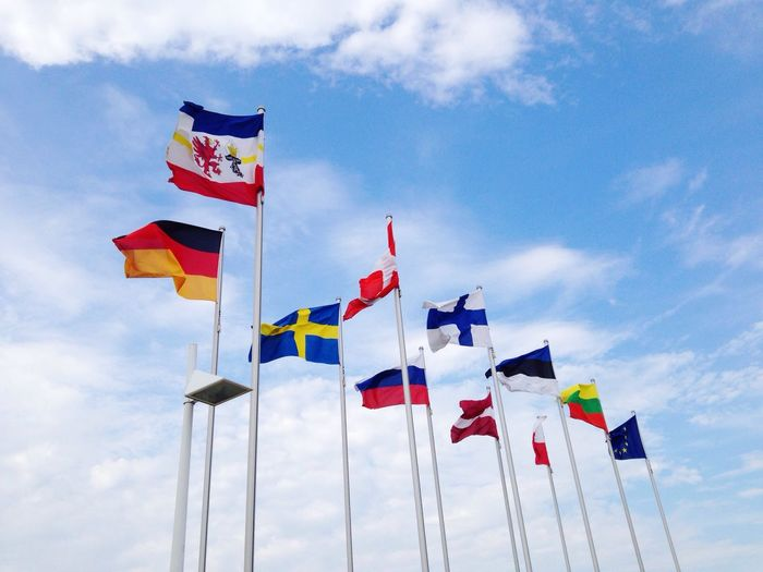 Low Angle View Of National Flags Against Sky
