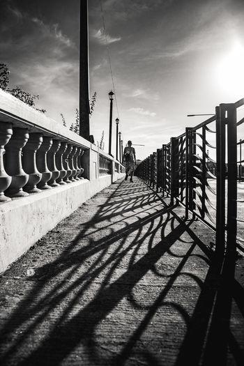 Shadow of woman walking on bridge against sky