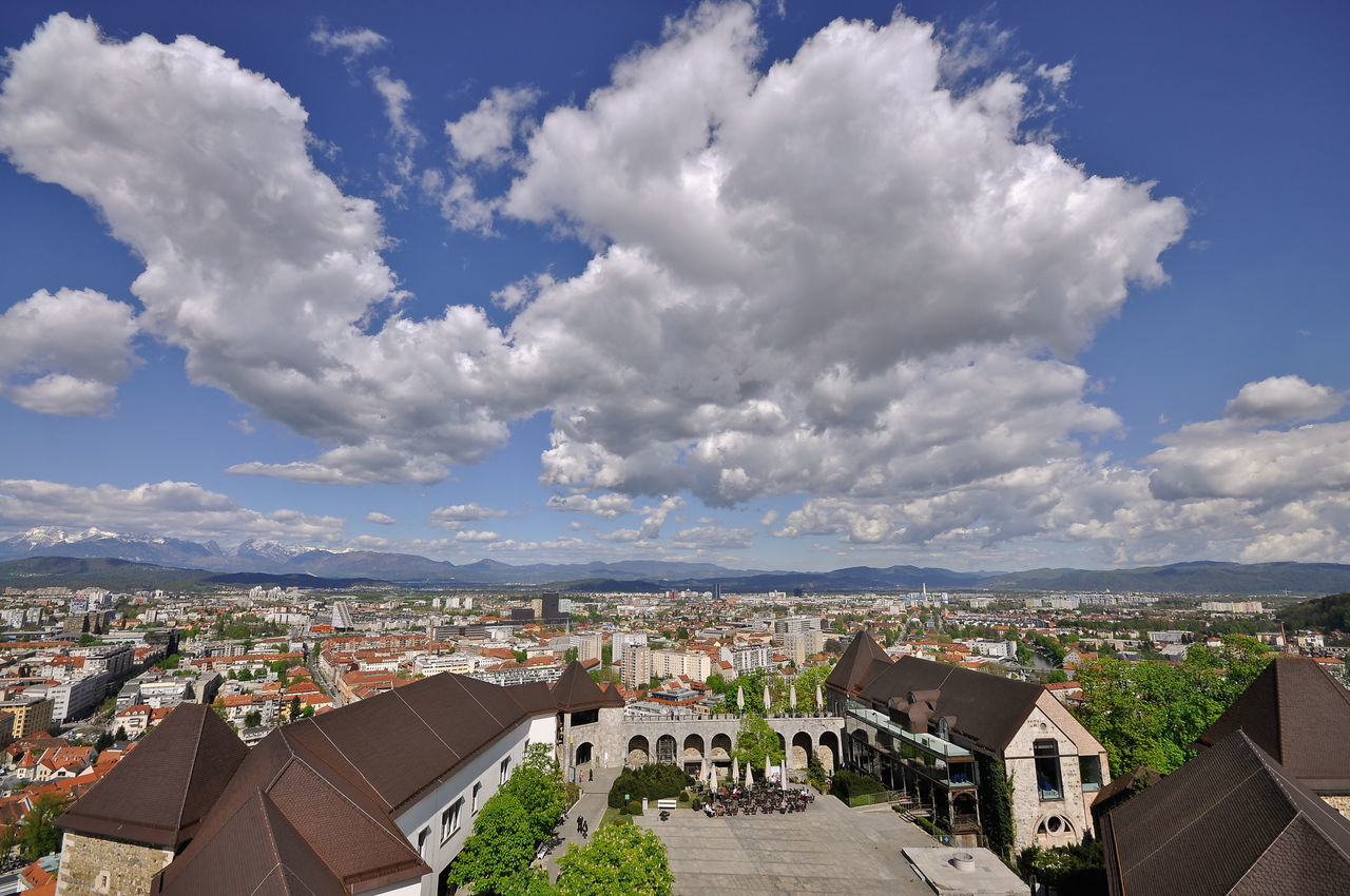 architecture, built structure, building exterior, cloud - sky, sky, crowded, high angle view, day, cityscape, town, city, roof, outdoors, residential building, community, tree, nature, residential, tiled roof