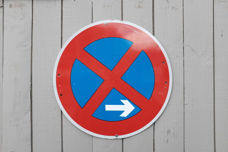 Close-Up Of No Stopping Sign On Wooden Wall