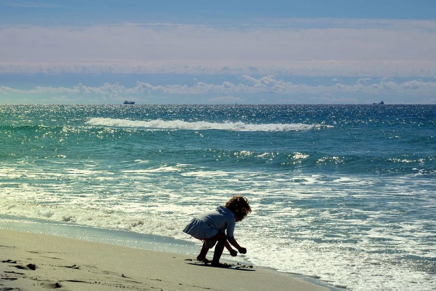 Kid at the beach Blue Sky White Clouds Beach Beauty Of Nature Child Playing At The Beach Horizon Over Water Horizontal Symmetry Peaceful Reflecting Water Sand Tranquil Scene Water Crest Waterfront Wave