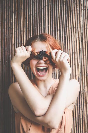 Young woman shouting while holding hair over eyes