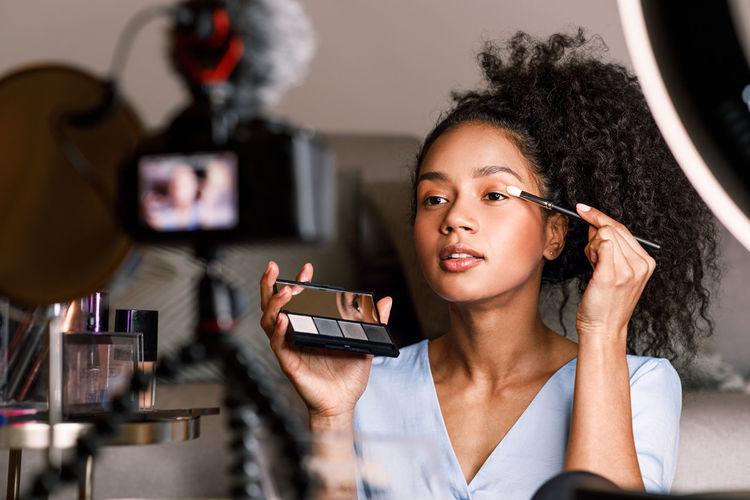 Smiling One Person Technology Indoors  Lifestyles Vlogger Blogger Filming Ring Light Sitting Skin Tone Pallette Holding Podcast Tutorial Brush Looking DSLR Screen Applying Curly Hair Course Online  Social Media