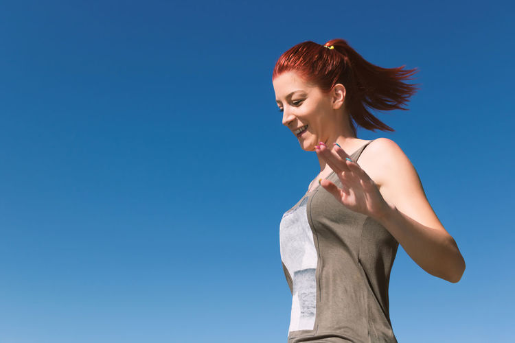 Low angle view of woman standing against blue sky