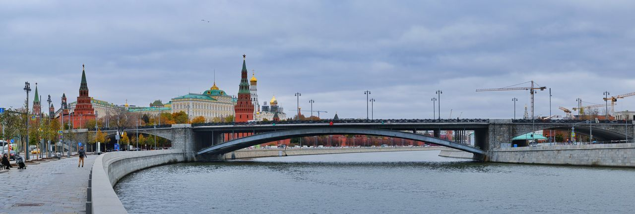 Bridge over river against buildings in city,moscow russia