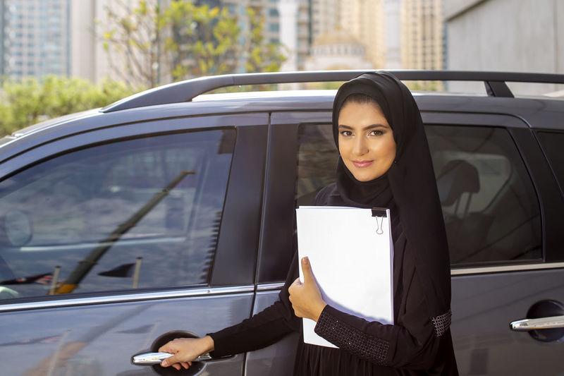 Portrait of woman in burka standing by car