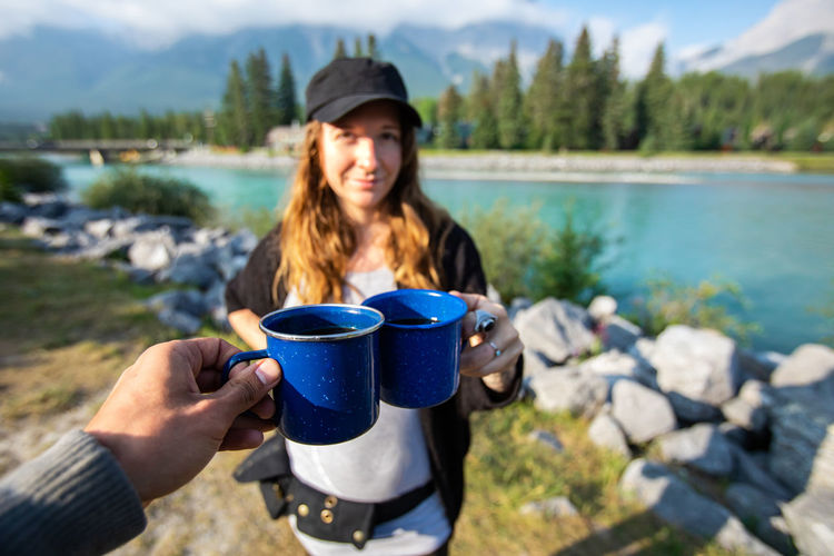 Young woman holding coffee cup by lake
