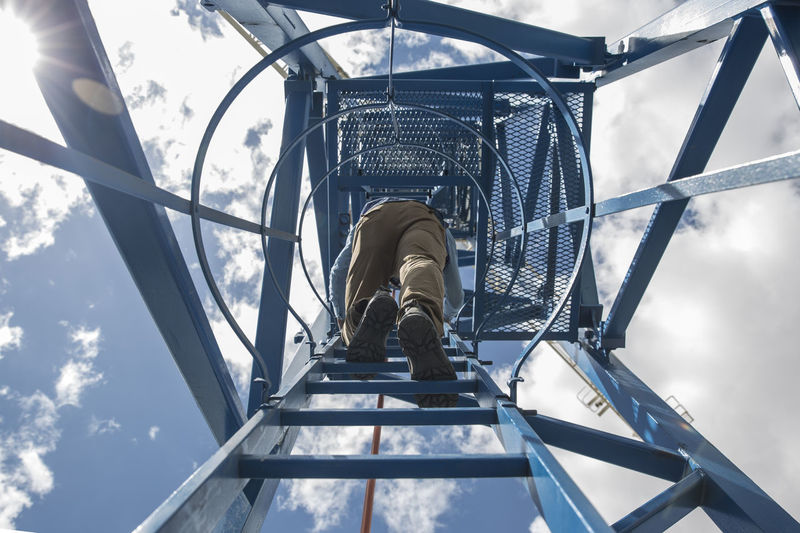 Low angle view of man standing in playground against sky