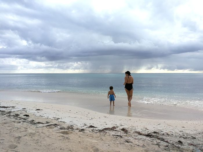 Rear View Woman Walking With Son On Shore At Beach Against Cloudy Sky