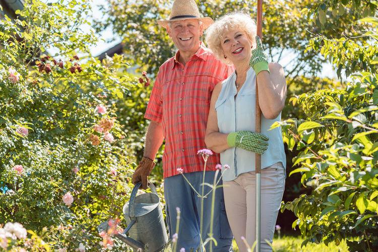 Portrait Of Smiling Senior Couple Standing At Backyard