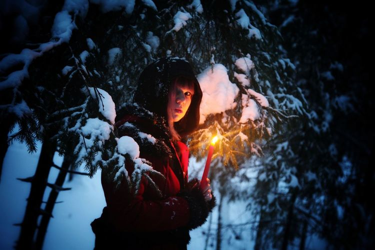 Portrait of young woman holding red illuminated candle by trees in winter