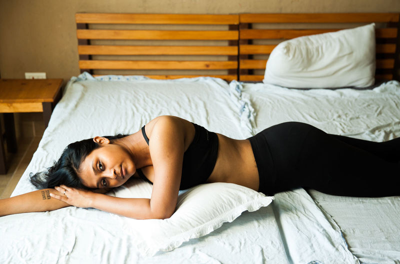 A girl in a sports outfit on a bed in the Himalayas. Girl Wearing Sports Bra In B Girl Sitting On Bed Girl Lying On Bed In Sports Attire Boudoir Photography A Girl Relaxing On Bed Girl Wearing Black Sport Outfit On Be Indian Girl In A Sporty Outfit Me Time In A Room Boudoir Natural Light