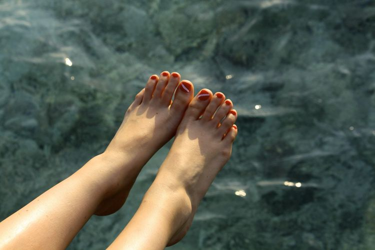 Female feet above water surface