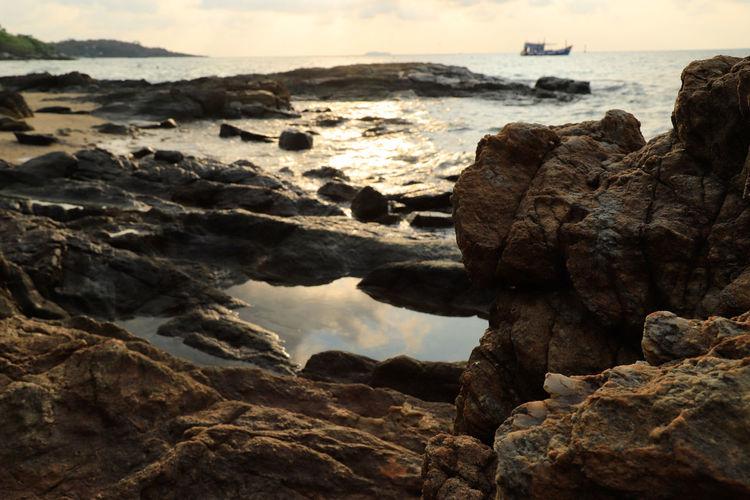 Rock formation on beach against sky