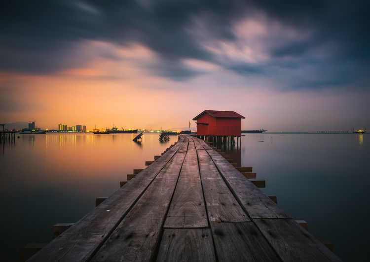 Empty wooden pier over lake against sky during sunset