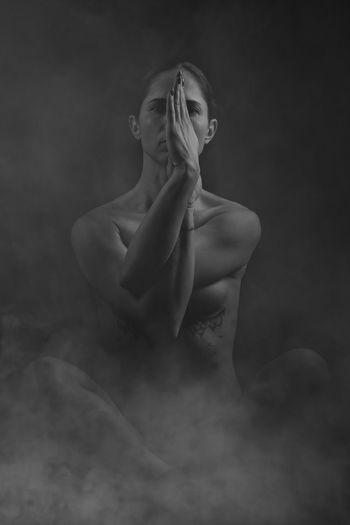 Portrait Of Naked Female Model Practicing Yoga Against Black Background