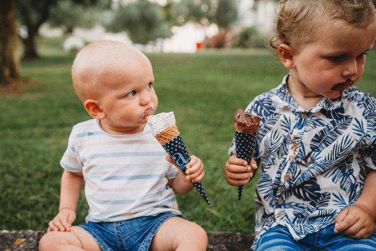 Cute boy sitting on ice cream outdoors